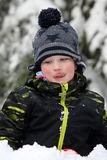 Little boy playing with snow a licking his face Royalty Free Stock Photos