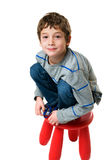 Little boy on a stool. Six year old boy up on a stool looking at the camera with a mischievous grin studio shot isolated on white Stock Image