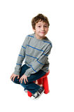 Little boy on a stool. Six year old boy sitting on a red stool making a funny face at the camera Royalty Free Stock Photography