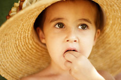 Little boy in straw hat eats Stock Image