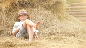 Little boy in a straw hat naps in the stack of hay taking a break from his choirs stock footage