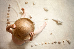 Little boy with straw hat, sitting on the ground, sea shells aro Stock Photo