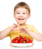 Little boy with strawberries Stock Photos