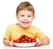 Little boy with strawberries Stock Images
