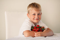 Little boy with strawberry Stock Photos
