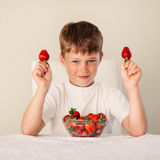 Little boy with strawberry Stock Images
