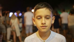 Little boy on the street at night in the crowd stock video footage