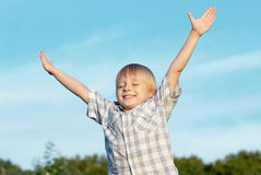 Little boy with stretched hands to sky Stock Images