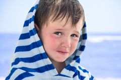A little boy in a striped bathrobe at the seashore with atopic dermatitis looks slyly and smiles,. A little boy in a striped bathrobe at the seashore with atopic Royalty Free Stock Images