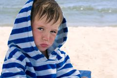 A little boy in a striped bathrobe at the seashore with atopic dermatitis was offended and pouted his lips, royalty free stock image