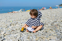 Little boy in striped blanket sitting on the pebbles beach and p Royalty Free Stock Photography