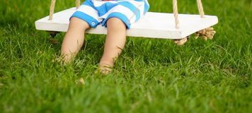 Little boy in a striped bodyguard swings on a swing stock photo
