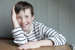 Little boy in striped shirt. Portrait of little boy in striped sailor shirt laughing in the back of the class Royalty Free Stock Image