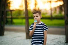 A little boy in a striped T-shirt is eating blue ice cream.Spring, sunny weather.  stock images