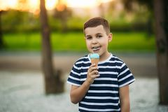 A little boy in a striped T-shirt is eating blue ice cream.Spring, sunny weather.  royalty free stock image