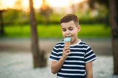 A little boy in a striped T-shirt is eating blue ice cream.Spring, sunny weather.  stock image