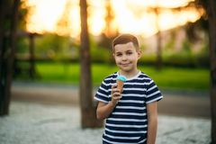 A little boy in a striped T-shirt is eating blue ice cream.Spring, sunny weather.  royalty free stock photography