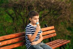 A little boy in a striped T-shirt is eating blue ice cream.Spring, sunny weather.  royalty free stock images