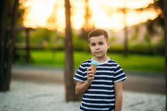 A little boy in a striped T-shirt is eating blue ice cream.Spring, sunny weather royalty free stock photo