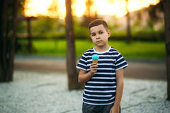 A little boy in a striped T-shirt is eating blue ice cream.Spring, sunny weather. Stock Photo