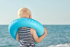 Little boy in a striped t-shirt and a life ring around his neck is standing and looking at the sea royalty free stock photo