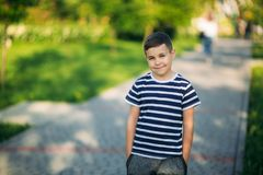 Little boy in a striped t-shirt looks through binoculars .Spring, sunny weather.  stock image