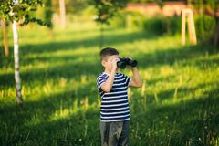 Little boy in a striped t-shirt looks through binoculars .Spring, sunny weather.  royalty free stock photo