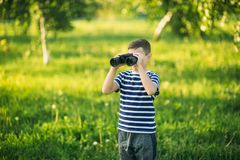 Little boy in a striped t-shirt looks through binoculars .Spring, sunny weather.  stock images