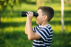 Little boy in a striped t-shirt looks through binoculars .Spring, sunny weather.  stock photo