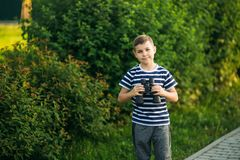 Little boy in a striped t-shirt looks through binoculars .Spring, sunny weather.  royalty free stock photos