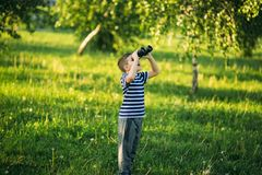 Little boy in a striped t-shirt looks through binoculars .Spring, sunny weather.  royalty free stock images