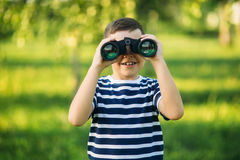 Little boy in a striped t-shirt looks through binoculars .Spring, sunny weather. Royalty Free Stock Image