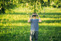 Little boy in a striped t-shirt looks through binoculars .Spring, sunny weather. Royalty Free Stock Photography