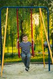 A little boy in a striped T-shirt is playing on the playground, Swing on a swing.  royalty free stock image