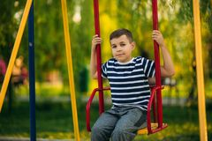 A little boy in a striped T-shirt is playing on the playground, Swing on a swing.  stock images