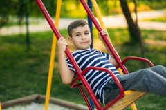 A little boy in a striped T-shirt is playing on the playground, Swing on a swing. Child is smiling and cheering Royalty Free Stock Photos