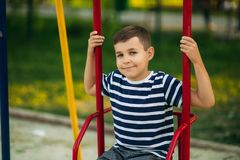 A little boy in a striped T-shirt is playing on the playground, Swing on a swing. Child is smiling and cheering Stock Photography