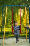 A little boy in a striped T-shirt is playing on the playground, Swing on a swing. Child is smiling and cheering Royalty Free Stock Images