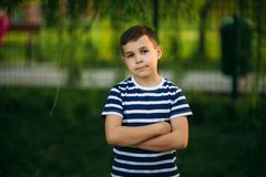 A little boy in a striped T-shirt is playing on the playground, Swing on a swing. Child is smiling and cheering Royalty Free Stock Photography
