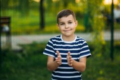A little boy in a striped T-shirt is playing on the playground, Swing on a swing. Child is smiling and cheering Royalty Free Stock Image