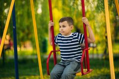 A little boy in a striped T-shirt is playing on the playground, Swing on a swing. Child is smiling and cheering Stock Image