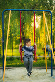 A little boy in a striped T-shirt is playing on the playground, Swing on a swing.Spring, sunny weather. Royalty Free Stock Photos