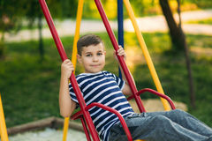 A little boy in a striped T-shirt is playing on the playground, Swing on a swing.Spring, sunny weather. Stock Photography
