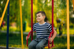 A little boy in a striped T-shirt is playing on the playground, Swing on a swing.Spring, sunny weather. Royalty Free Stock Image