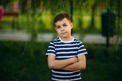 A little boy in a striped T-shirt is playing on the playground, Swing on a swing.Spring, sunny weather. Royalty Free Stock Images