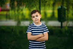 A little boy in a striped T-shirt standing in front of green background. Smiling and looking to the photographer.  stock photos