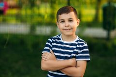 A little boy in a striped T-shirt standing in front of green background. Smiling and looking to the photographer.  royalty free stock image