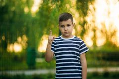 A little boy in a striped T-shirt standing in front of green background. Smiling and looking to the photographer. Boy. A little boy in a striped T-shirt standing stock photo