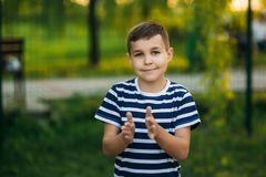 A little boy in a striped T-shirt standing in front of green background. Smiling and looking to the photographer. Boy. A little boy in a striped T-shirt standing royalty free stock images