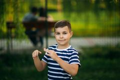 A little boy in a striped T-shirt standing in front of green background. Smiling and looking to the photographer. Boy. A little boy in a striped T-shirt standing royalty free stock image